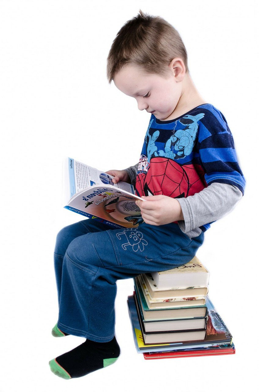 Image of boy reading on a stack of books